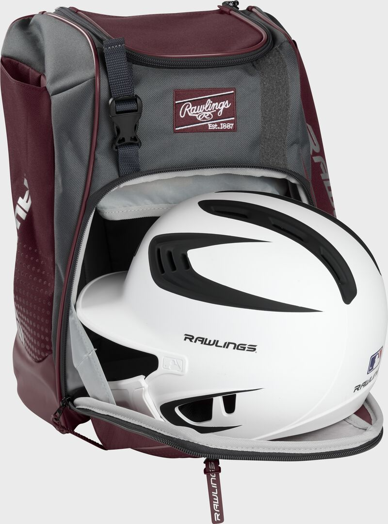A white/black helmet in the main compartment of a maroon Rawlings Franchise backpack - SKU: FRANBP-MA