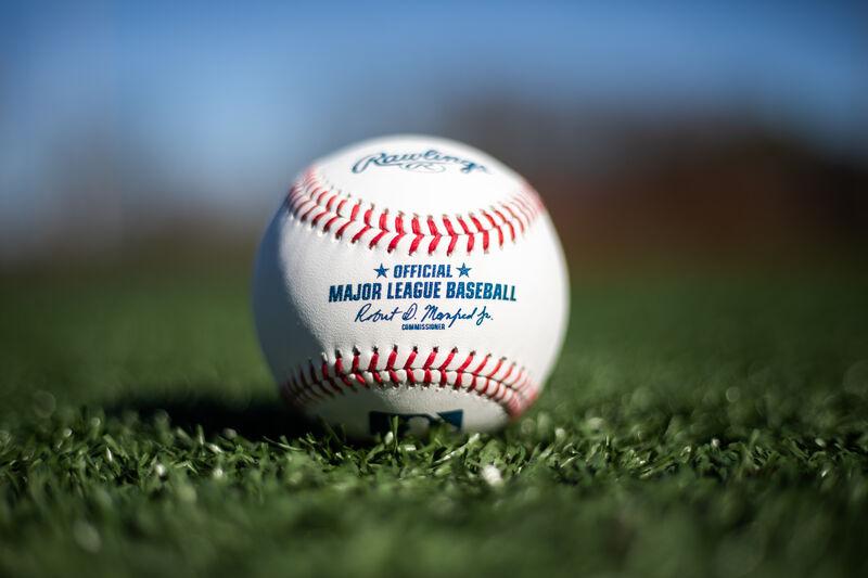 A Rawlings MLB baseball lying in the grass on a field - SKU: ROMLB