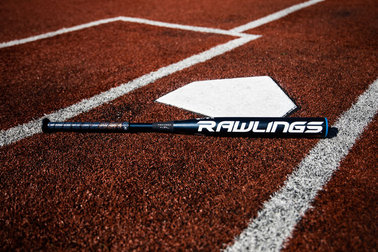 A Rawlings end loaded Quatro Pro bat lying on a field next to home plate - SKU: FPPE10