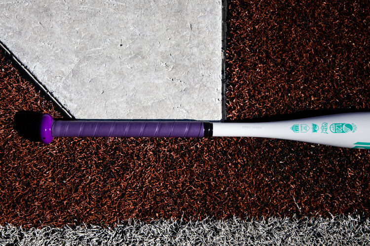 Purple batting grip of a Rawlings Ombre fastpitch bat lying next to home plate - SKU: FPZO11