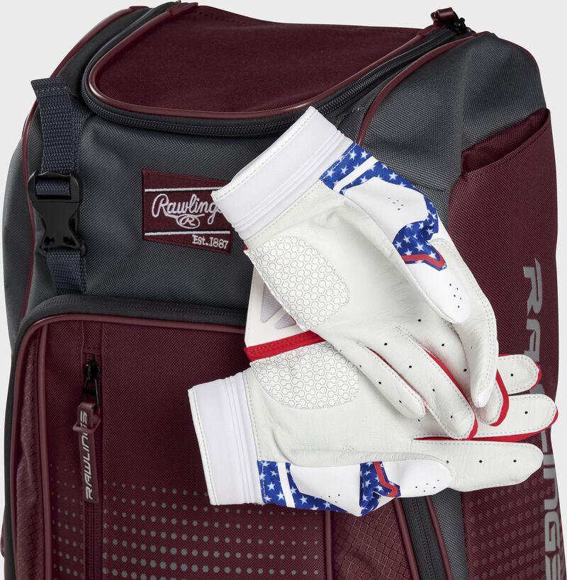 Two batting gloves hanging on the front Velcro strap of a Franchise baseball backpack - SKU: FRANBP-MA