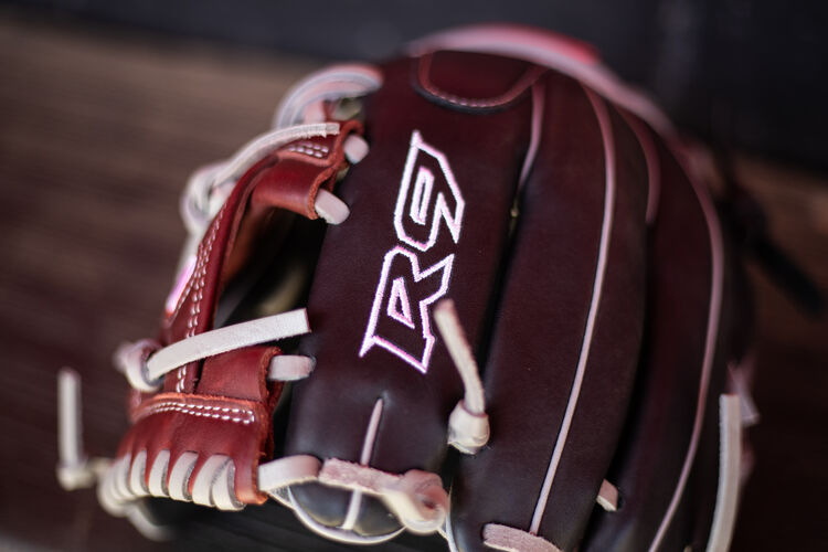R9 Logo on the index finger of a R9 Series infield glove sitting on the bench in a dugout - SKU: R9204-2BSG