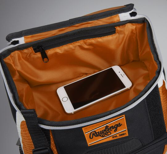 Top accessory pocket of a black/orange R500 equipment backpack holding a phone
