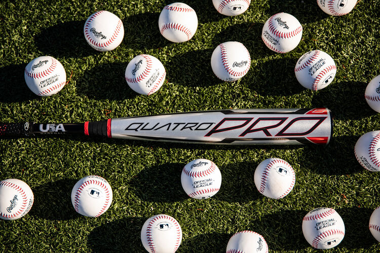 A gray Rawlings Quatro Pro youth bat on a field with baseballs around it - SKU: US1Q8