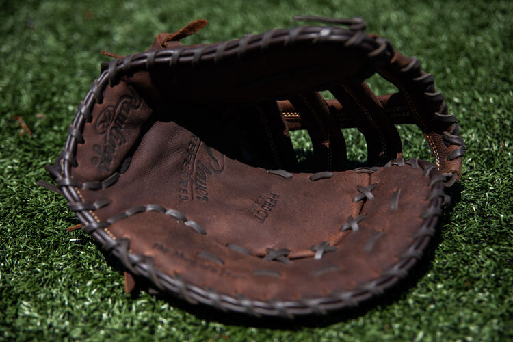 Brown palm of a Rawlings Player Preferred recreational first base mitt lying on a field - SKU: PFBDCT