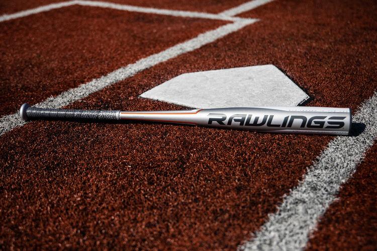 A silver Rawlings 5150 baseball bat lying on a field at home plate - SKU: BBZ53