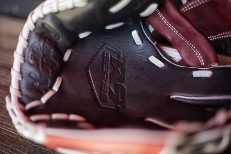 Black palm of a R9 Series infield glove lying on a bench in a dugout - SKU: R9204-2BSG