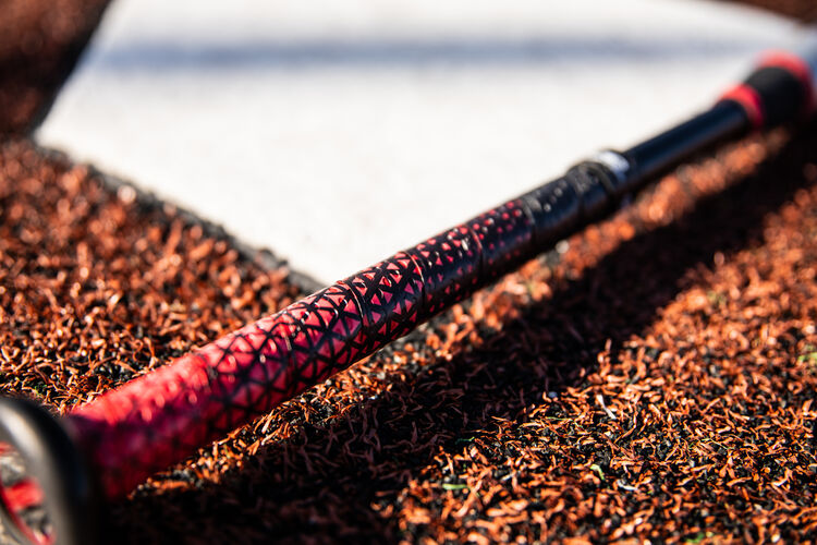 Red/black Lizard Skins batting grip on a USA -8 Quatro Pro by home plate - SKU: US1Q8