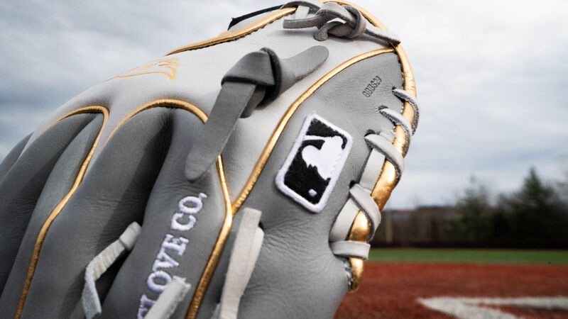 The MLB logo on the grey pinkie of a HOH exclusive infield glove on a field - SKU: PRO204W-2GW