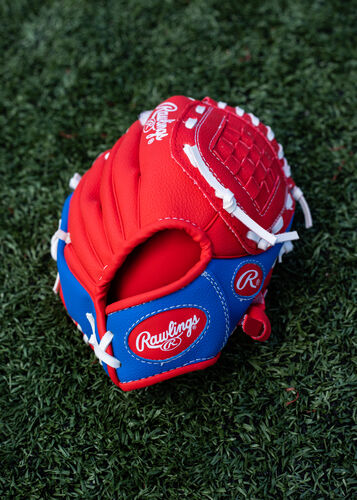 Red Rawlings logo on a red/blue Players Series youth glove lying on a field - SKU: PL91SR