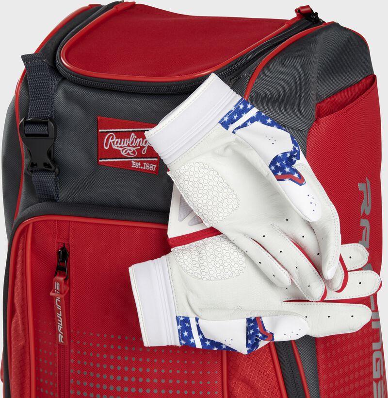 Two batting gloves hanging on the front Velcro strap of a Franchise baseball backpack - SKU: FRANBP-S
