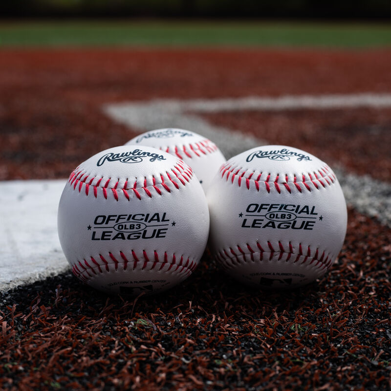 Three Rawlings Official League baseballs lying next to home plate on a field - SKU: OLB3