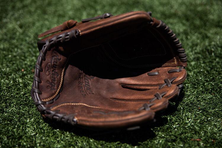 A brown palm of a Player Preferred softball glove lying on a field - SKU: P120BFL