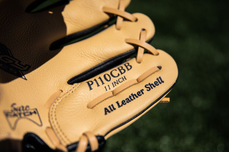 Camel pinkie of a Rawlings Prodigy baseball glove lying on a field - SKU: P110CBB
