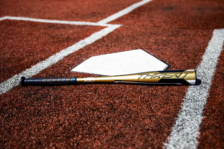A gold Rawlings 2020 USA Threat bat lying on a field next to home plate - USZT12