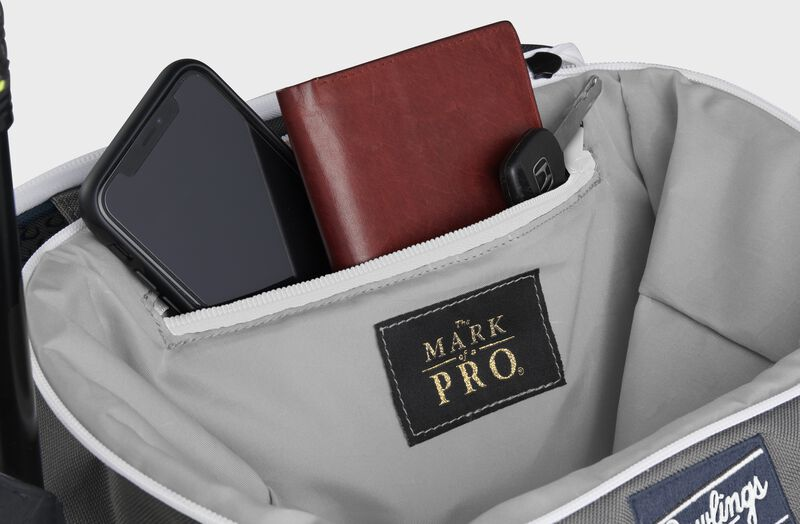 Zippered pocket in the top storage compartment of a navy Impulse backpack with a phone, wallet and keys - SKU: IMPLSE-N