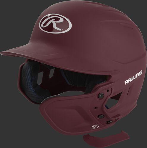A maroon MEXTR attached to a Mach batting helmet with the removable TPU piece off to show the hardware