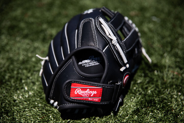 Rawlings patch on the wrist strap of a RSB recreational glove lying on a field - SKU: RSB130GBH
