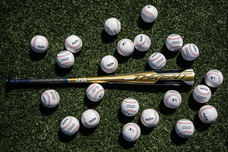 A Rawlings Threat USA bat lying on a field surrounded by baseballs - SKU: USZT12