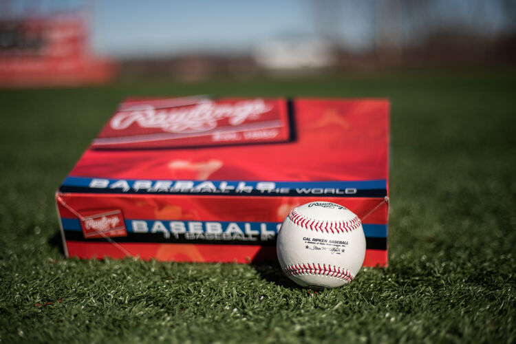 A Cal Ripken baseball lying in front of a ball box on a field - SKU: RCAL1