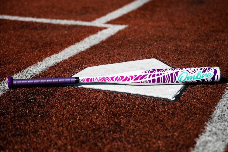 A Rawlings Ombre fastpitch bat lying on home plate of a field - SKU: FPZO11