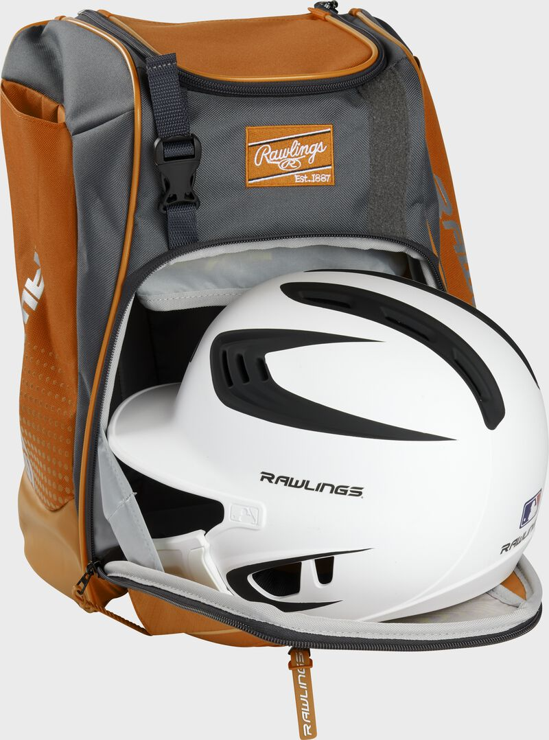 A white/black helmet in the main compartment of an orange Rawlings Franchise backpack - SKU: FRANBP-O
