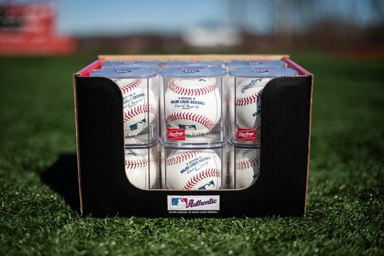 A box of a dozen MLB baseballs in display cubes sitting in the grass on a field - SKU: ROMLB-R