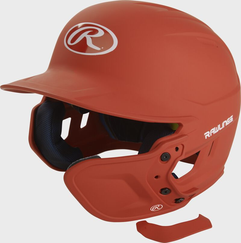 A matte burnt orange MEXT attached to a Mach batting helmet showing the hardware