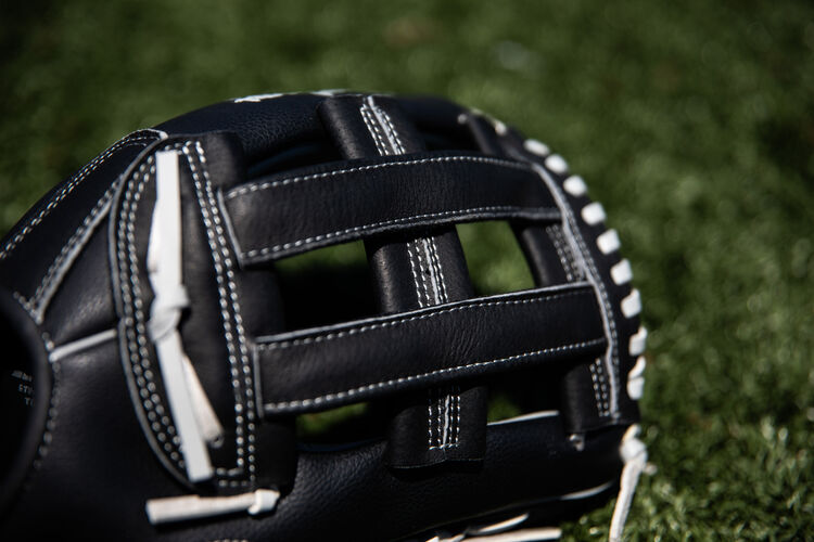 A black H-web on a Rawlings RSB softball glove with a field in the background - SKU: RSB130GBH