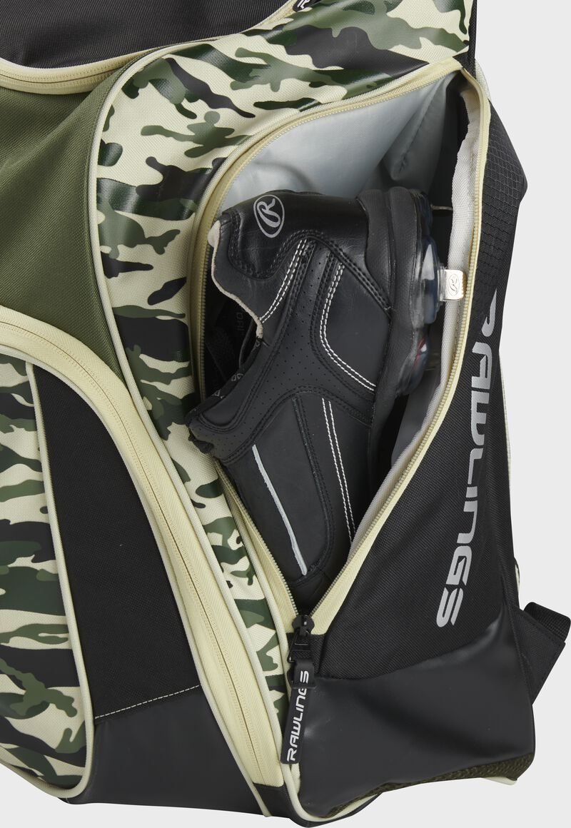 A cleat in the side cleat pocket of a camo Legion baseball backpack - SKU: LEGION-CAMO