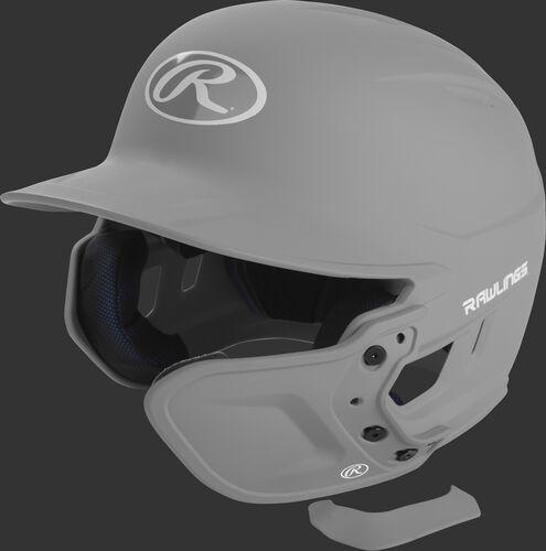 A silver MEXTR attached to a Mach batting helmet with the removable TPU piece off to show the hardware