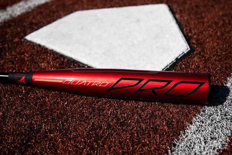 Red barrel of a Rawlings 2020 Quatro Pro baseball bat lying next to home plate - SKU: BBZQ3