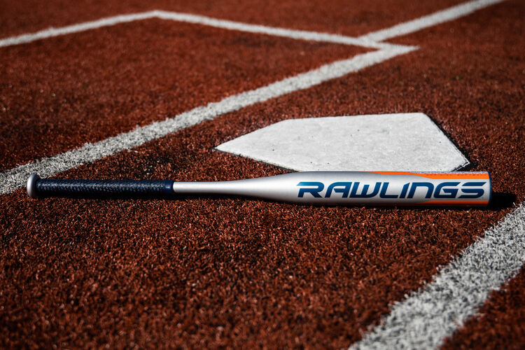 A Rawlings Storm fastpitch bat lying next to home plate - SKU: FPZS13