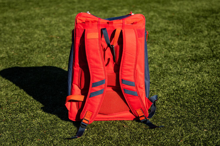 Red back of a USA Legion backpack sitting on a field with red shoulder straps - SKU: LEGION-USA