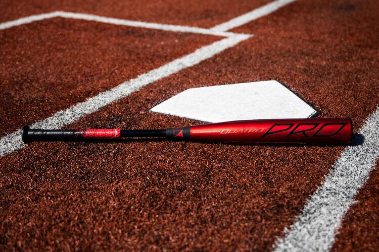A 2020 Quatro Pro BBCOR bat lying next to home plate - SKU: BBZQ3