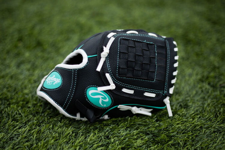 A black Players youth glove with a mint Oval-R lying on a field - SKU: PL10BMT