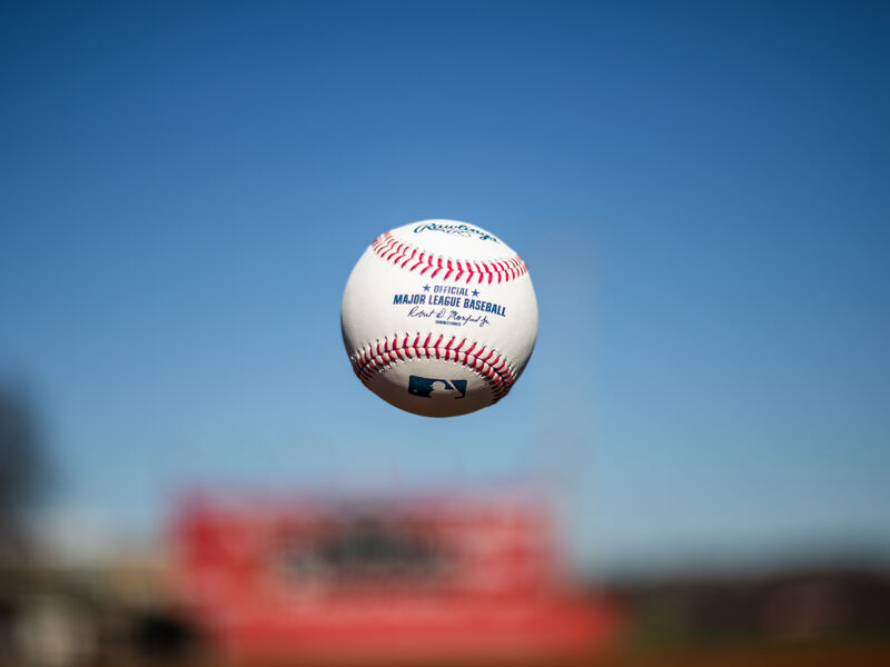 A Rawlings Official MLB baseball being tossed in the air with the sky in the background - SKU: ROMLB