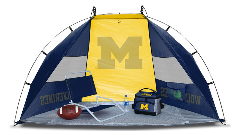 A Michigan Wolverines sideline sun shelter set up with a chair, cooler, football and water bottle - SKU: 00973083111