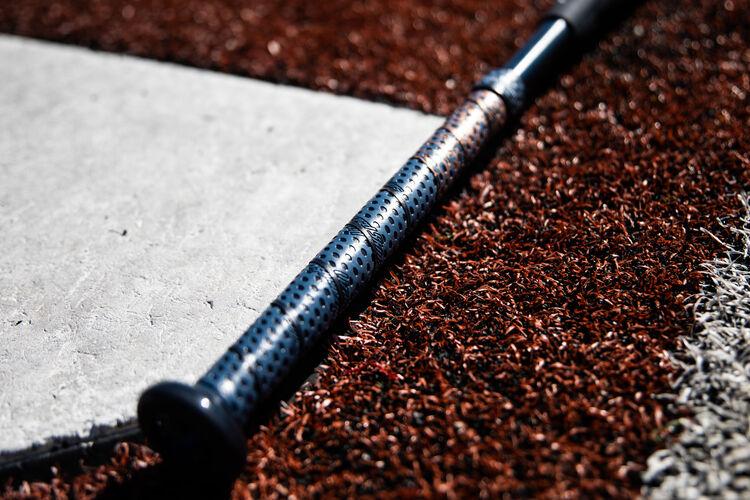 Lizard Skins batting grip on a Rawlings Quatro Pro end load bat lying next to home plate - SKU: FPPE9