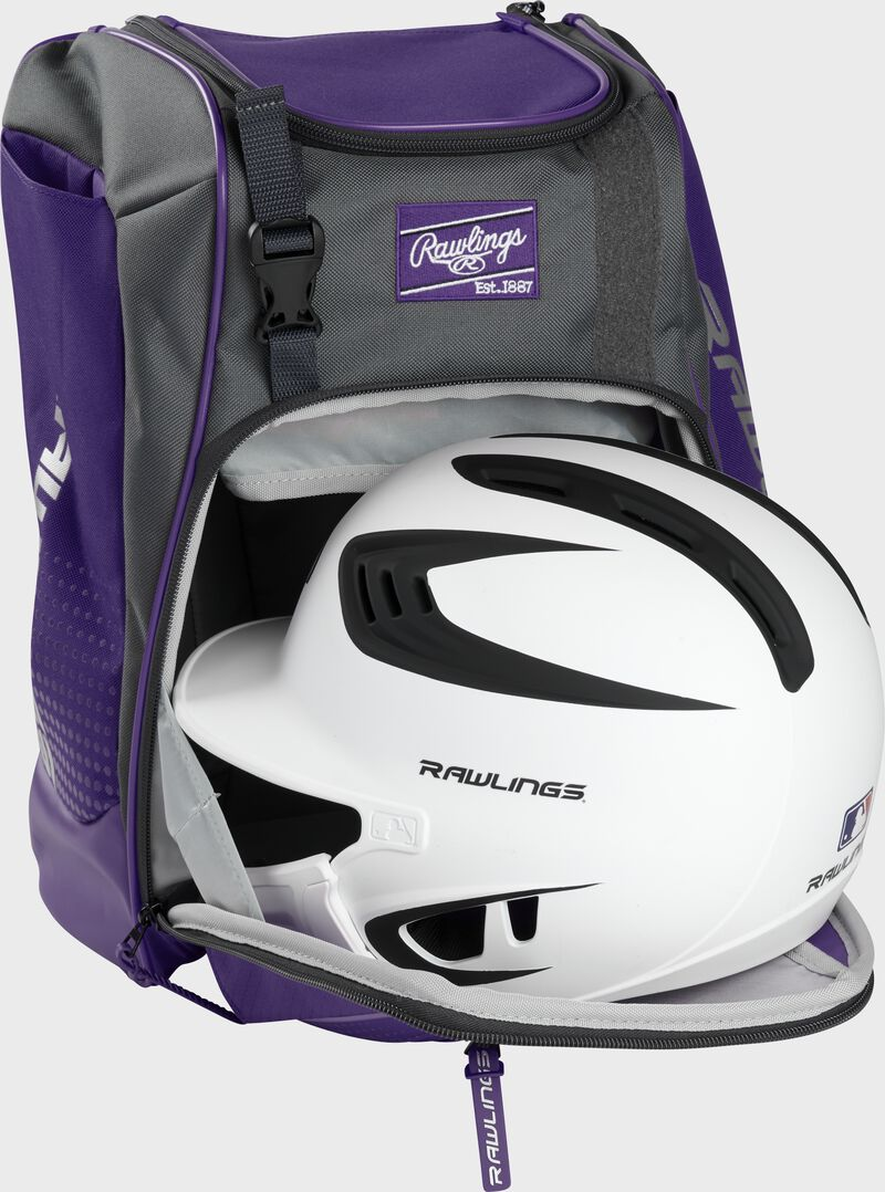 A white/black helmet in the main compartment of a purple Rawlings Franchise backpack - SKU: FRANBP-PU
