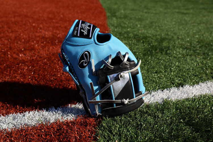 A Columbia blue/black HOH ColorSync 5.0 I-web glove standing on its finger tips on a field - SKU: PRO204-2BCB