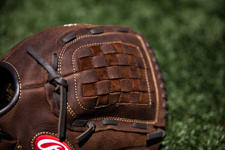 A brown Basket web on a 12-Inch Player Preferred recreational glove on a field - SKU: P120BFL