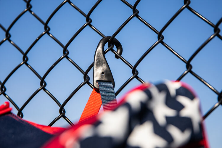 The fence hook on a USA Rawlings Legion baseball backpack hanging on a fence - SKU: LEGION-USA