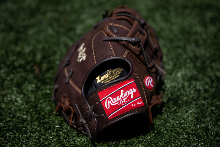 Rawlings patch on the wrist strap of a Player Preferred first base mitt lying on a field - PFBDCT