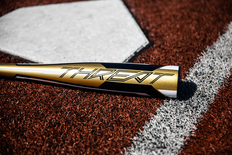 Gold barrel of a Rawlings Threat bat lying next to home plate - SKU: USZT12