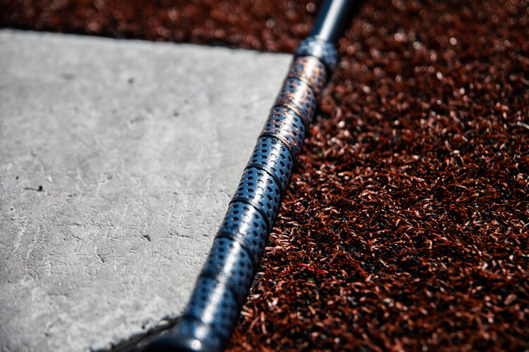 Lizard Skins batting grip on a Quatro Pro fastpitch softball bat next to home plate - SKU: FPZP9
