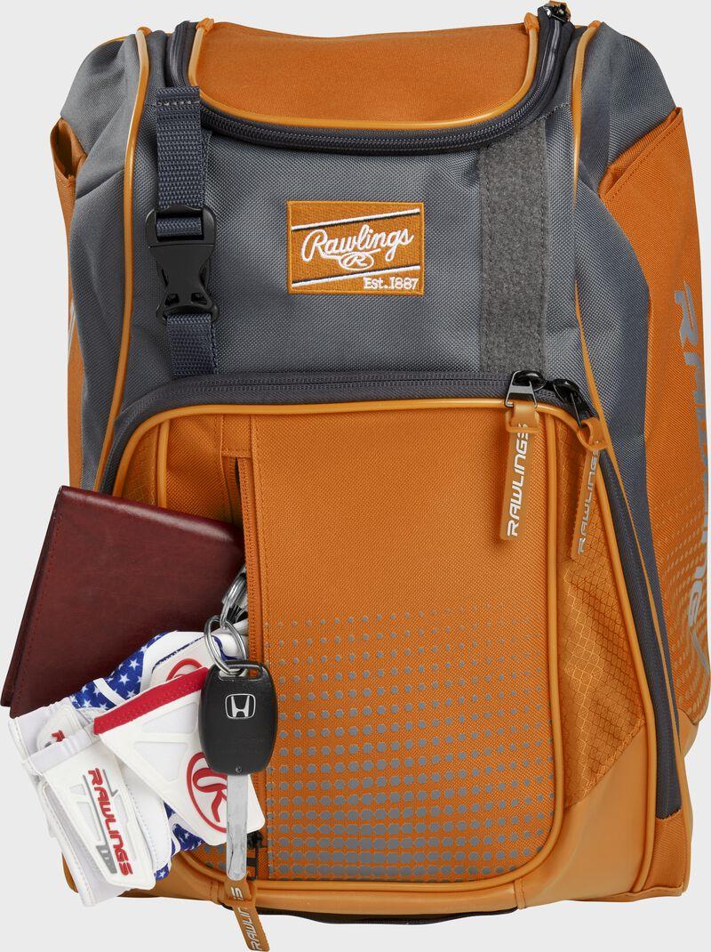 Wallet, keys, and batting gloves in the front valuables pocket of an orange Franchise baseball bag - SKU: FRANBP-O