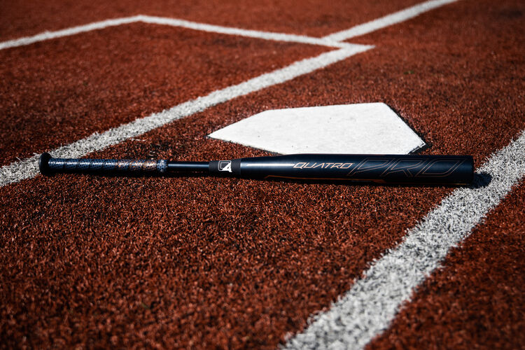A Quatro Pro -9 fastpitch bat lying on a field at home plate - SKU: FPZP9