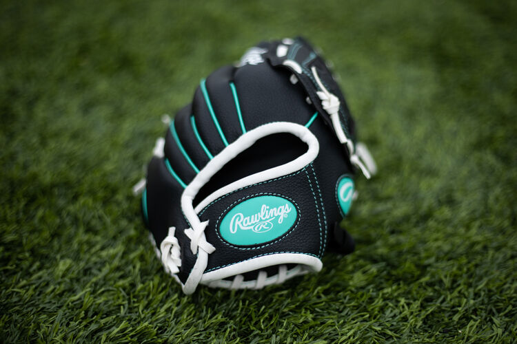 Mint Rawlings logo on a wrist strap of a youth Players glove lying on a field - SKU: PL10BMT