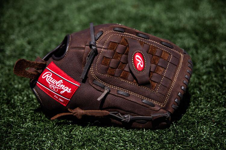 A brown Player Preferred Basket Web glove lying on a field - SKU: P140BPS